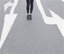 Symbolbild Person die auf der Straße zwischen Richtungsmarierungen steht.