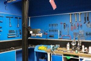 Eine Werkstatt mit diversen Werkzegen an der Wand und einem Arbeitsplatz mit Werkzeugen, Ölspray und weiteren Dingen