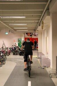 Ein Monteur fährt auf dem reparierten Fahrrad auf einem markiertem Weg in dem Ladengeschäft. Der Weg führt durch Reihen ausgestellter Fahrräder.