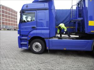 Ein Berufskraftfahrer schließt die Leitungen eines Sattelaufliegers an der Zugmaschine an