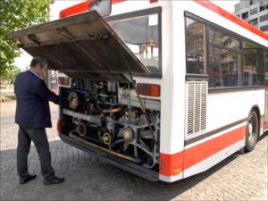 Ein Berufskraftfahrer prüft den Ölstand im Motorraum eines Bus