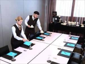 Eine Hotelfachfrau und ein Hotelfachmann decken eine Essenstafel ein