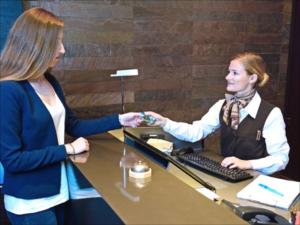 Eine Hotelfachfrau übergibt am Hotelempfang einem Hotelgast die Schlüsselkarte