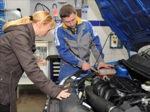 Ein KFZ_Mechatroniker zeigt einer Kundin ein Bauteil am Motor eines Autos