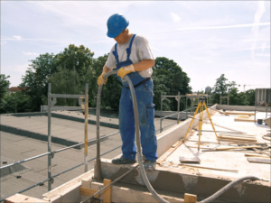 Ein Maurer füllt mit eiem Schlauch flüssigen Beton in eine Verschalung.