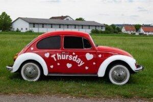 VW Käfer auf einer Wiese mit Aufschrift 'Tuesday'