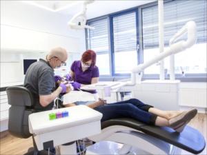 EIn Zahnarzt und eine zahnmedizinsiche Fachangestellte behandeln eine Patientin