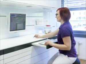 Eine Zahnmedizinische Fachngestellte gibt Daten am Copmuter ein.